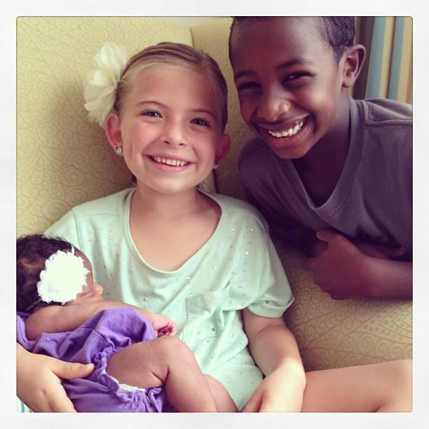 Brother and sister holding newborn. transracial adoptive family. Global Munchkins