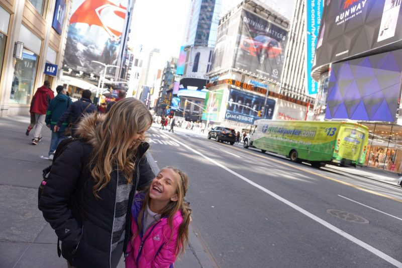 Mon and daughter embracing in time square. Mom and daughter are happy and smiling.