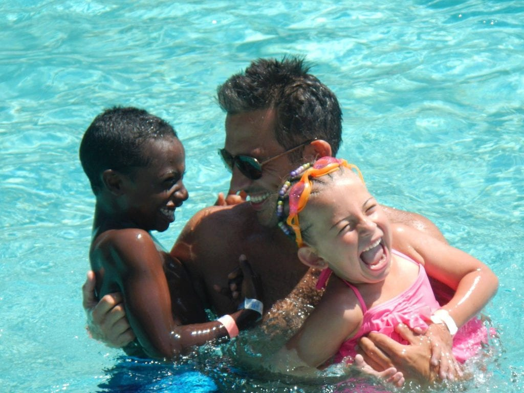 Transracial adoptive family laying in pool at Disney's Beach Club