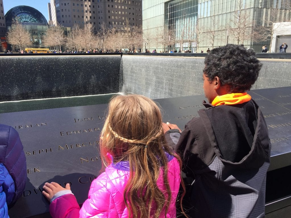 A little white girl next to a little black boy looking at the 9/11 Memorial | Global Munchkins