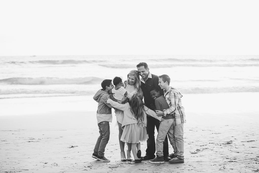 Family huddling together and embracing on a beach   Global Munchkins
