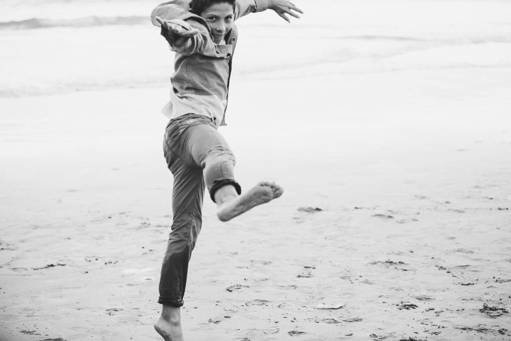 Boy jumping on beach   Global Munchkins