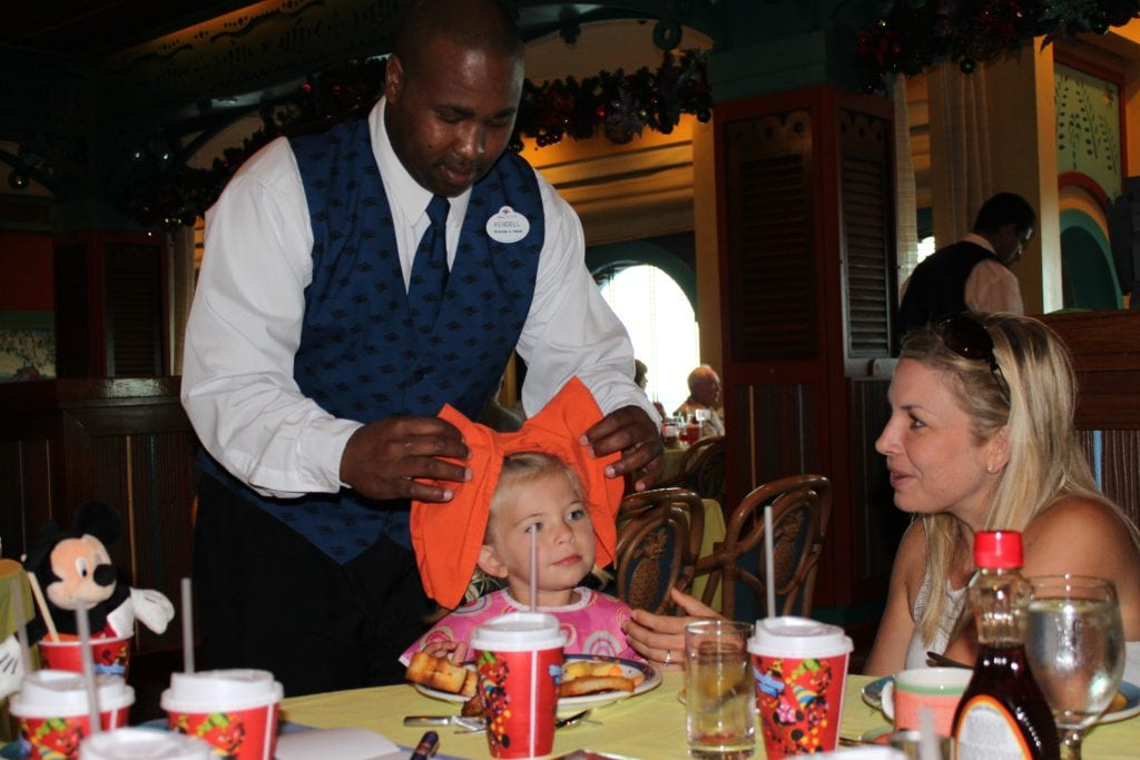 Waiter making a big Minnie Bow for little girl at dining table onboard Disney Cruise Line | Global Munchkins
