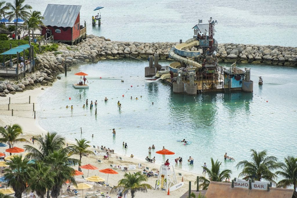 "Guests slide and splash on Pelican Plunge, an exciting water play area located within swimming distance from the shore at Castaway Cay. The 2,400-square-foot floating platform has two water slides—an enclosed corkscrew slide and a 140-foot-long open slide—that take guests on a twisting ride, ending with a splash into the lagoon. A giant ""bucket dump"" and water cannons soak guests on the platform. (Matt Stroshane, photographer)"